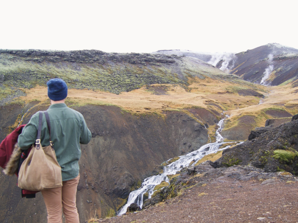 Traveler with bag looking at distant waterfall in Iceland