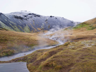 Steaming Reykjadalur Hot Spring River with snowy Icelandic mountains