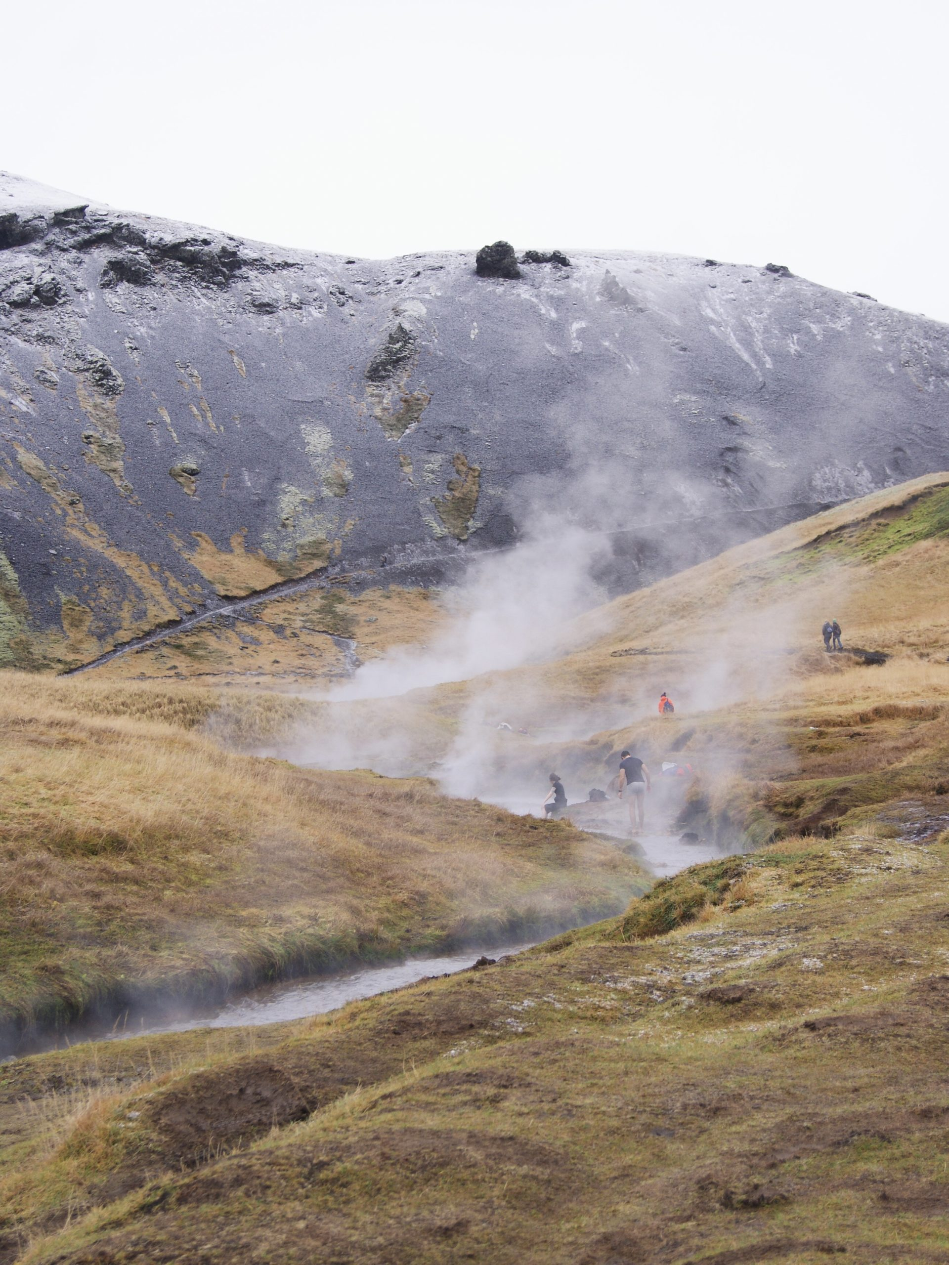 Tourists soaking in the natural Reykjadalur Hot Springs of Iceland