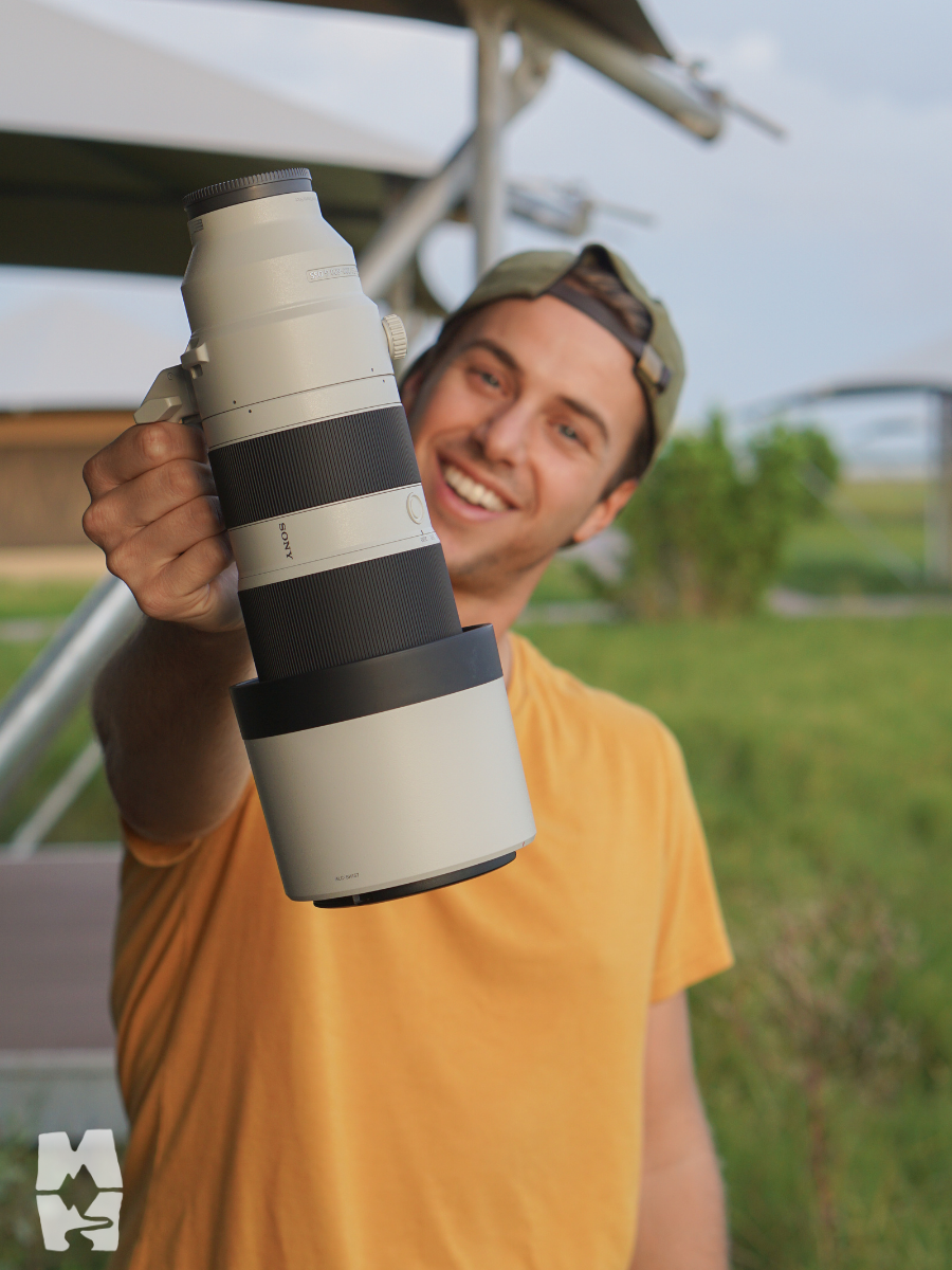 Young man holding out a large telephoto camera lens