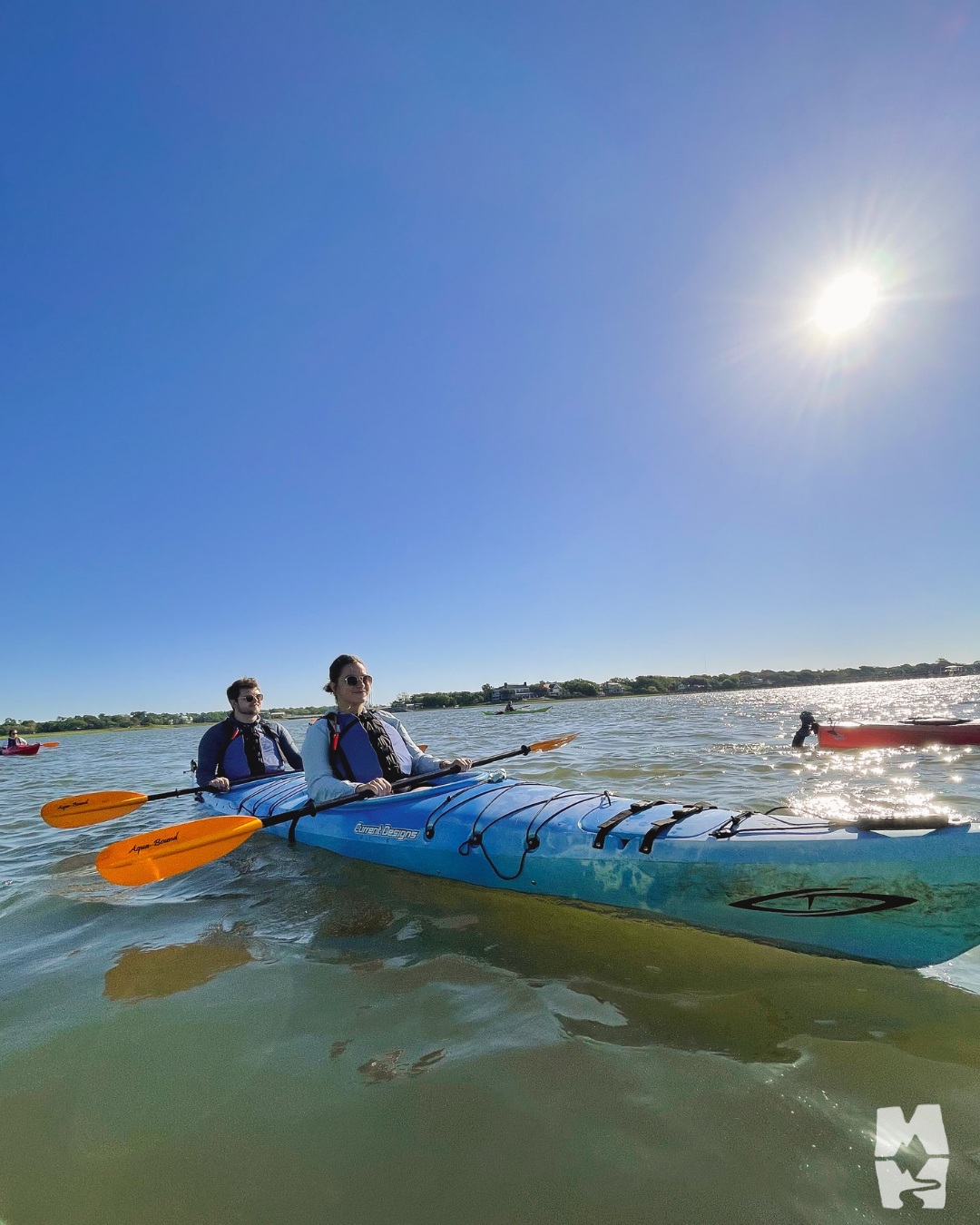 two adults kayaking in a tandem kayak on the ocean