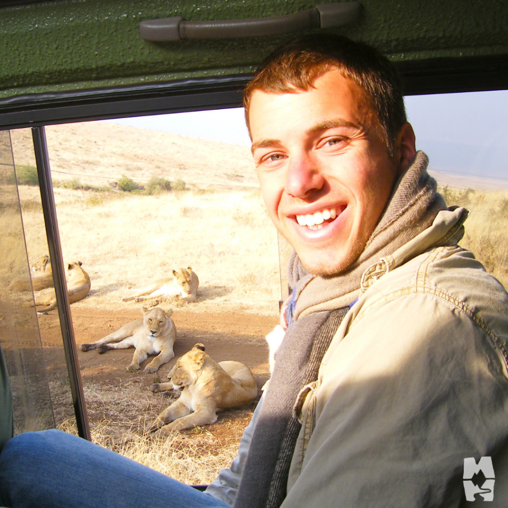 Young man smiling next to a pride of lions while on safari in Tanzania.